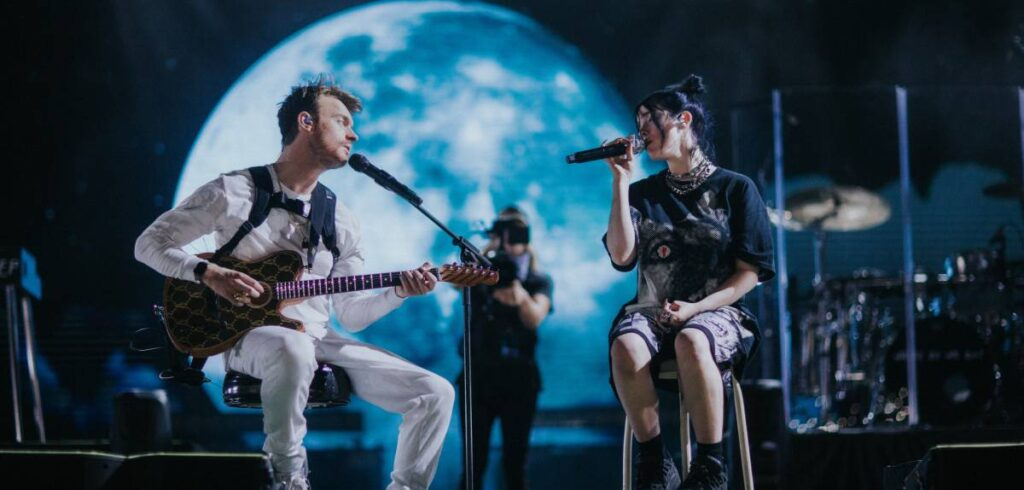 """Billie Eilish and Finneas O'Connell on stage in """"Billie Eilish: The World's A Little Blurry,"""" premiering globally February 26, 2021 on Apple TV+."""